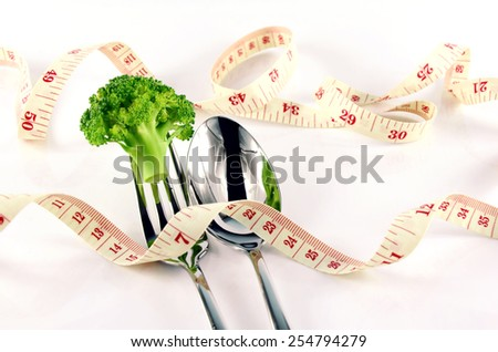 Broccoli, Tape Measure, Fork and Spoon in Waistline and Weight Control Concept by Diet Control. - stock photo