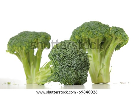 Broccoli vegetable standing on a white shiny table isolated on white background. - stock photo