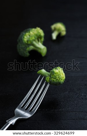 Broccoli with fork on black stone plate background, Diet concept with broccoli - stock photo