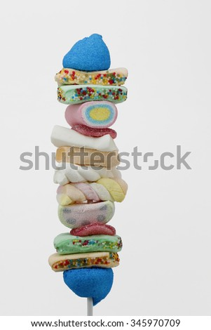 Brochette of sweet candies, in a white background
