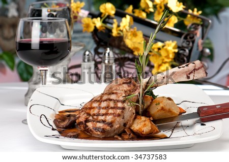 Broiled center cut veal chop with sauteed onions and mushrooms and table setting with wine, - stock photo