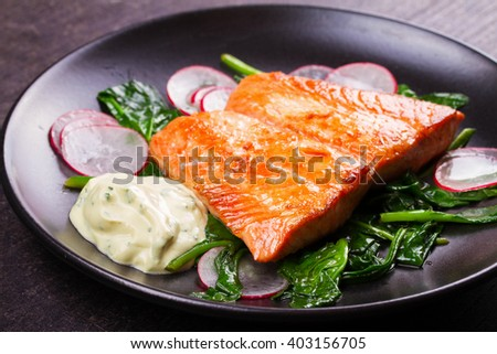 Broiled salmon with radish and spinach, served on black plate