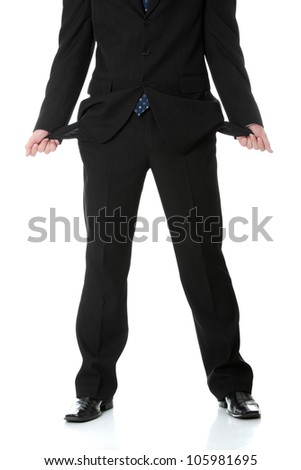 Broke business man in black suit and tie showing his empty pockets after loosing all his money. Isolated on white background.