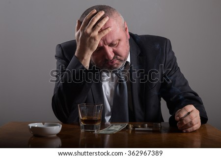 Broke Business man with a glass of whiskey and cigarette - stock photo