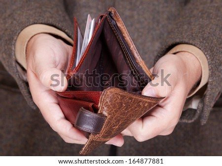Broke businessman showing brown leather empty wallet. Business concept- finance and poor economy. - stock photo