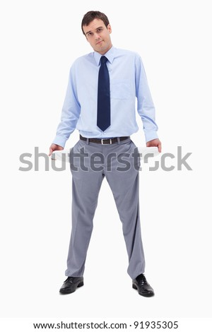 Broke businessman showing his empty pockets against a white background