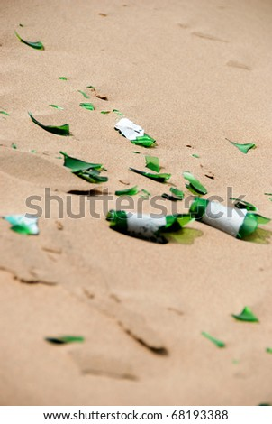 Broken beer bottle in the sand dunes - stock photo