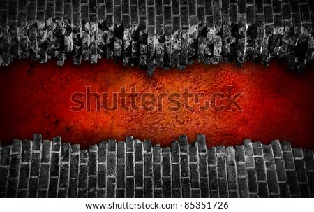 Broken black brick wall  with large red hole - stock photo