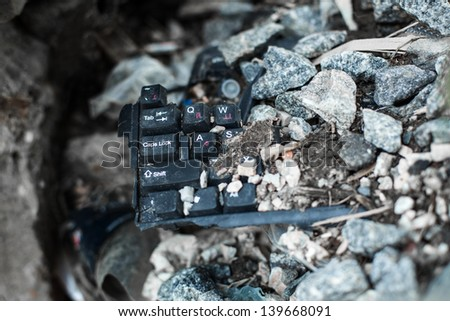 broken black keyboard lying on the garbage under the stone - stock photo