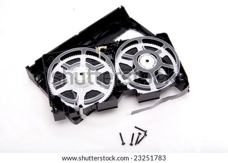 Broken black video cassette on white background - stock photo