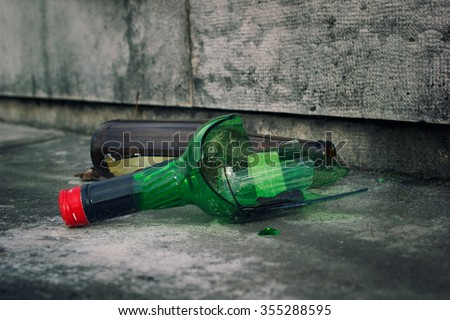 Broken bottles, green and brown, with red bottle cap on a pavement - stock photo