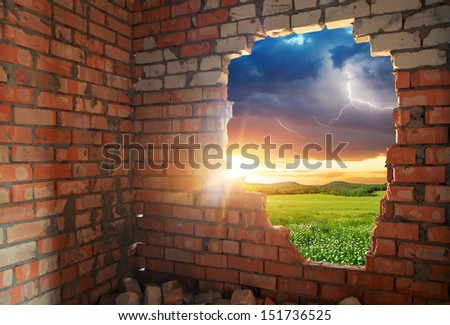 Broken bricks wall and landscape. Conceptual composition. - stock photo