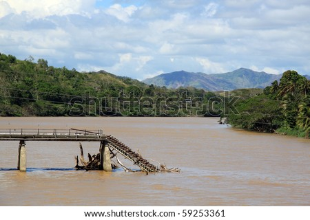 Broken bridge on the river in Fiji - stock photo