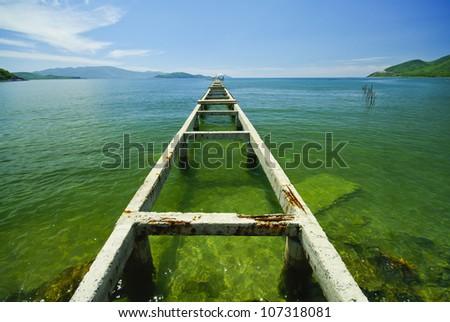 Broken bridge to the emerald sea - stock photo