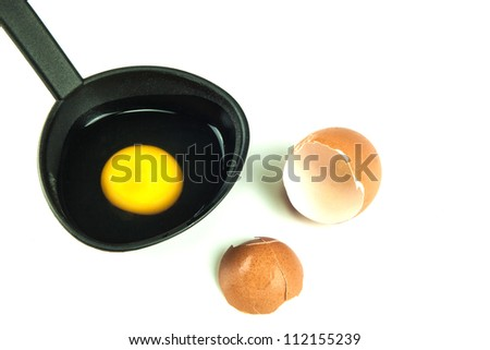 Broken brown egg with raw egg in black spoon - stock photo
