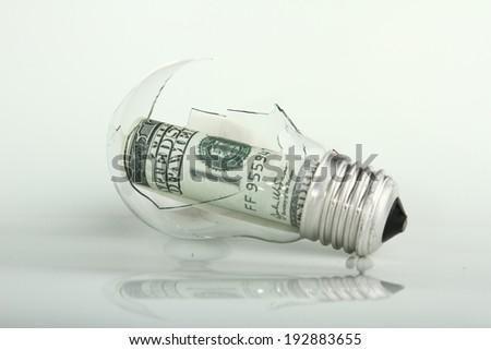 broken bulb with dollar - stock photo