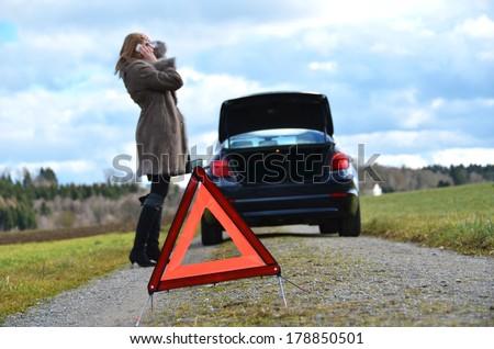 Broken car, girl and warning triangle - stock photo
