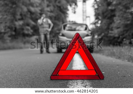 Broken car on the road and red warning triangle - black and white concept