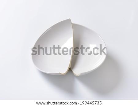 Broken ceramic bowl on white background - stock photo