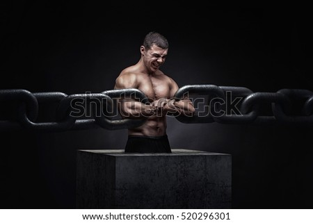 Broken Chain - Freedom Concept . Brutal man bodybuilder athlete holding a chain on a black background. metaphor