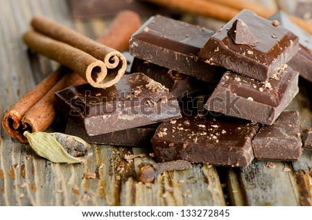 Broken chocolate bar and spices on wooden table. Selective focus - stock photo