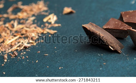 Broken chocolate bar, chips and powder. Shallow depth of field. - stock photo