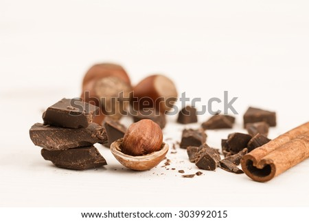 Broken chocolate bar, hazelnut and cinnamon on wooden background, close-up