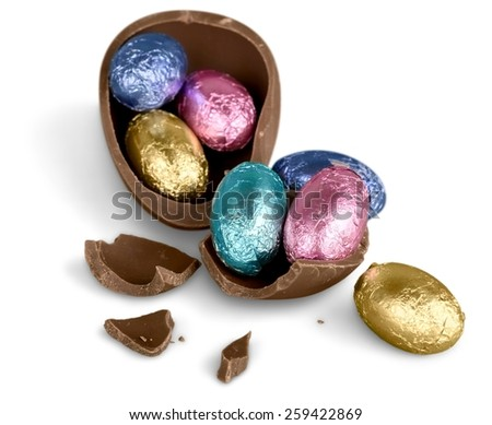 Broken chocolate Easter egg with colorful candies on white background  - stock photo