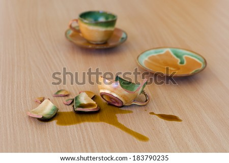 Broken  cup with spilled coffee on a table.  - stock photo