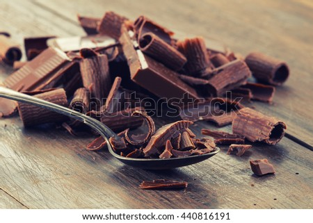 Broken dark chocolate and chocolate shavings on a wooden table - stock photo