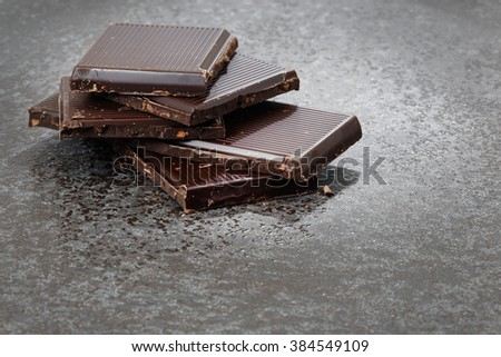Broken dark chocolate on a stone table
