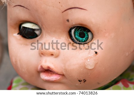 Broken doll crying. Concept Abandoned Person. Close up of an old doll`s face with tear - stock photo