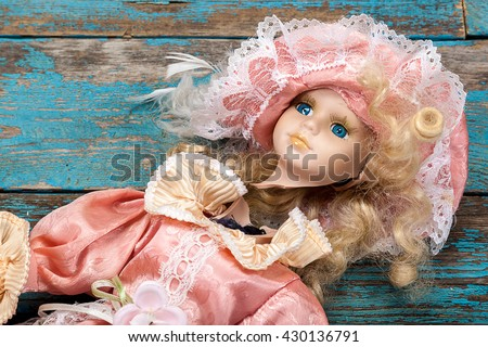 Broken doll on a wooden background.