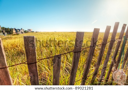 Broken down boardwalk fence in Maine sand dunes early on a summer morning - stock photo