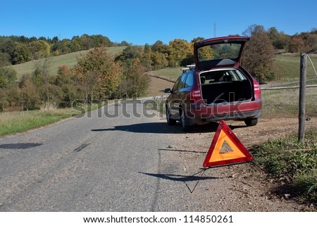 broken-down car on a deserted country road - stock photo