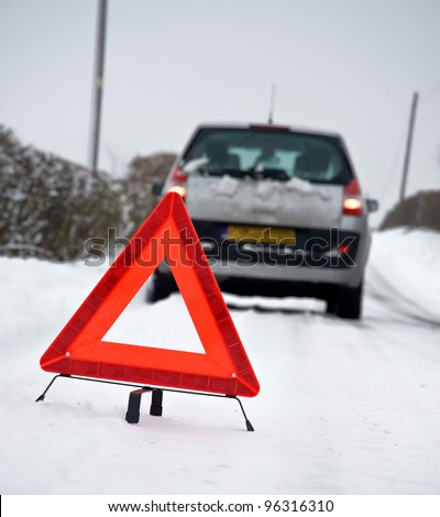 Broken down vehicle in winter snow conditions with red warning triangle - stock photo