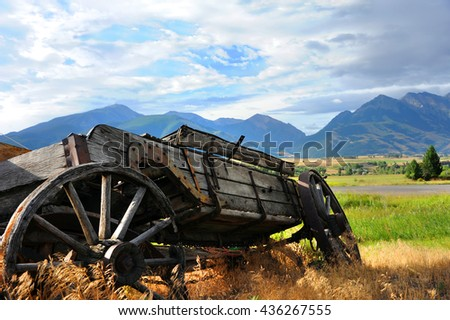 Broken down, wooden wagon sits overgrown with weeds.  It has a view of distant Absaroka Mountains in Paradise Valley, Wyoming. - stock photo