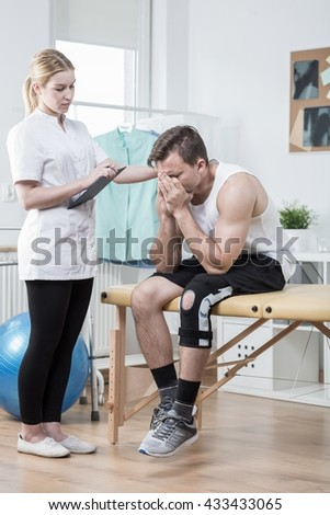 Broken down young man with hurtful sick knee
