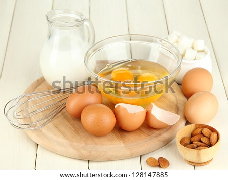 Broken egg in bowl and various ingredients next to them on wooden table close-up