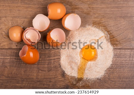 Broken egg lying in the heap of flour near the eggs shells on the wooden table. Top view - stock photo