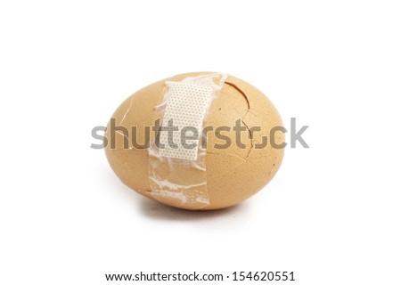 Broken egg with sticking plaster - stock photo