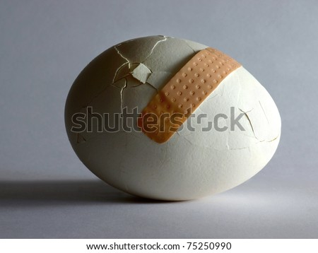 Broken egg with sticking plaster - stock photo