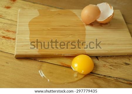 broken eggs on wooden table - stock photo