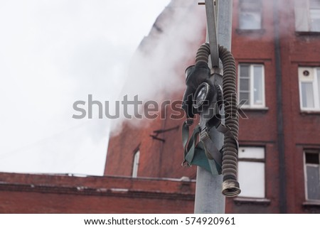 broken gas mask hanging on a pole on the outskirts of the city amid the smoke and the house with the Windows open