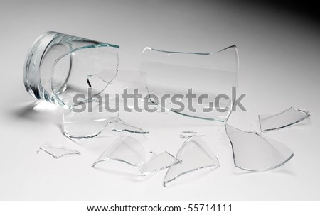 broken glass against grey background, concept of danger - stock photo