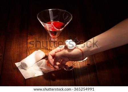 Broken glass and bloody hand closeup on dark background - stock photo