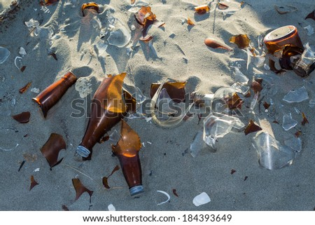 Broken glass bottles left in the sand. - stock photo