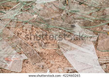 Broken glass fragments above grey. - stock photo