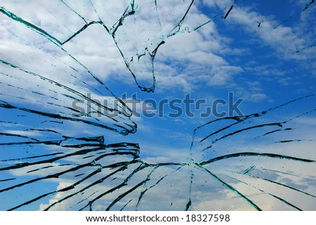 broken glass looking out to blue sky. possible concept for escaping a situation or contrast of peacefulness and violence - stock photo
