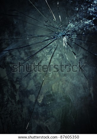 Broken glass over grey background. - stock photo